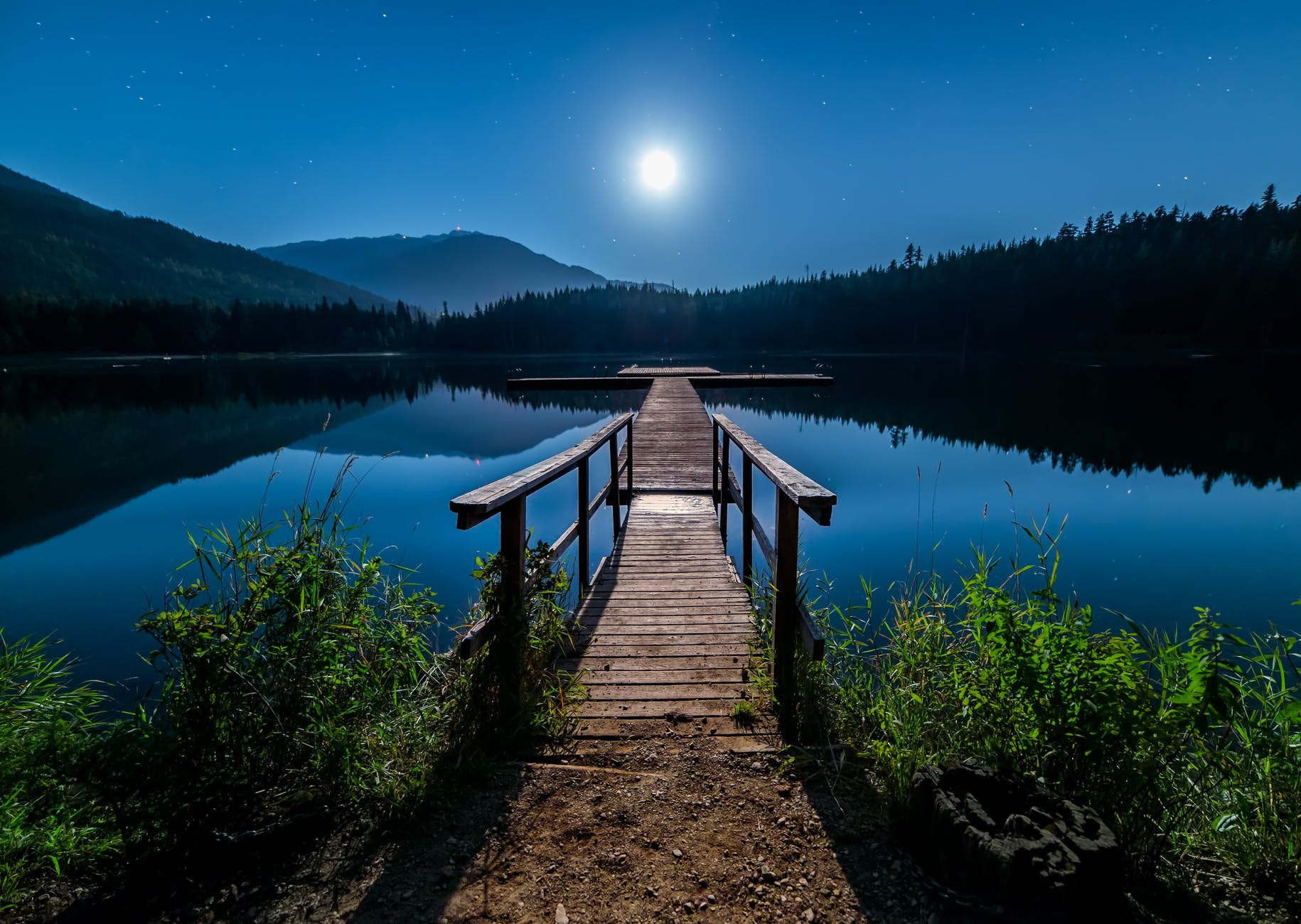 A brown dock leading towards a brightly moonlit lake. This symbolizes the peace and tranquility of the soul sanctuary in Berkeley, CA. A highly sensitive therapist can provide spritual guidance in this empath group at Joyful Empath.